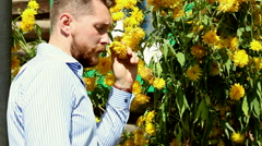 Young bearded man sniffing a flowers Stock Footage