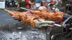 Fried crocodile meat on a barbeque for sale at the street's restaurant Stock Footage