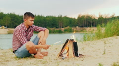 Young attractive man sitting by the fire alone. Fries marshmallow on a stick Stock Footage