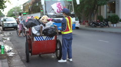 Cleaner is collecting garbage from ballot box on a roadside in the downtown at Stock Footage