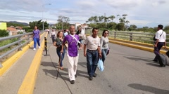 Man with cast and cane walking across Colombian-Venezuelan border (HD) Stock Footage