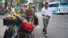 The moped with baskets full of fruits is parked on a roadside. Locals pass Stock Footage