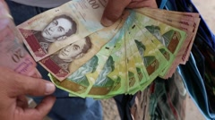 Man fans out Devalued Venezuelan money (HD) Stock Footage