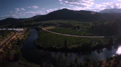 Aerial View: River Bend In Rural Farm Landscape/Countryside Mountains Stock Footage