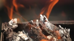 Branches of cherry wood stacked in a barbecue burning bright red flames Stock Footage