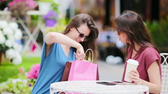 Two young girls at the outdoors cafe. Two women after shopping with bags sitting Stock Footage
