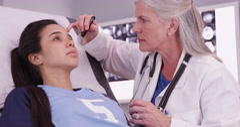 Mid aged caucasian doctor reviewing female hispanic athlete head trauma - stock footage