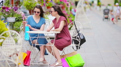 Two fashion colorful shoppers with bags shopping in openair cafe. Sale Stock Footage