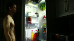 Night man stands at the open refrigerator. eating sandwich. hungry guy Stock Footage