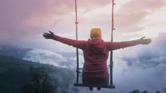 Woman on a swing over the ecuadorian mountains Stock Footage