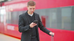 Young caucasian man with smarphone and luggage at station traveling by train Stock Footage