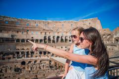Young mother and little girl hugging in Coliseum, Rome, Italy. Family portrait Stock Photos