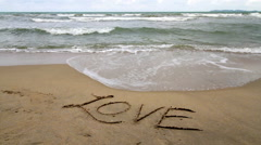 Love Written on the Sand Gets Washed Away by a Wave Stock Footage