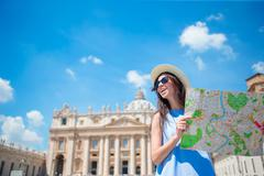 Happy young woman with city map in Vatican city and St. Peter's Basilica church Stock Photos