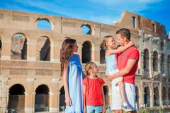 Happy family of four at italian vacation on Colosseum background in Rome Stock Photos