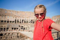 Little girl making selfie in Coliseum, Rome, Italy. Kid portrait at famous - stock photo