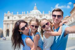 Happy young family taking selfie at St. Peter's Basilica church in Vatican city - stock photo