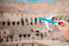 Closeup toy airplane on Colosseum background. Italian european vacation in Rome - stock photo
