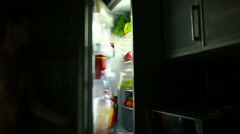 Man eating out of the refrigerator at night. eating apple Stock Footage