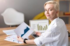 Woman analyzing some diagrams on table Stock Photos
