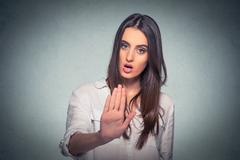 Annoyed angry woman with bad attitude giving talk to hand gesture Stock Photos