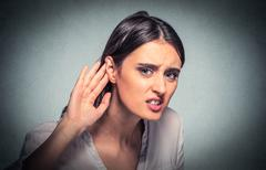 Closeup portrait young nosy woman hand to ear gesture trying carefully listen - stock photo