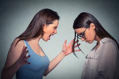 Angry woman abusing screaming at another scared nerdy one in glasses Stock Photos