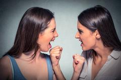 Two women fight. Angry girls looking at each other screaming Stock Photos