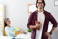 Positive man standing in the office - stock photo