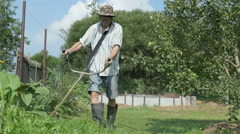 The worker cuts the grass with lawn string trimmer Stock Footage