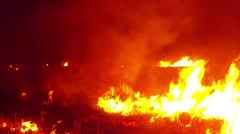 Tongues of Fire Raging Over the Field in the Darkness Closeup Stock Footage