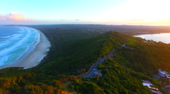 Mountain and beach road from above with dramatic sunset clouds in the distance Stock Footage