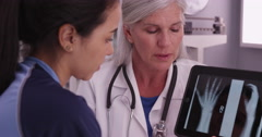 Mid aged doctor showing xrays on a tablet to a young female athlete - stock footage
