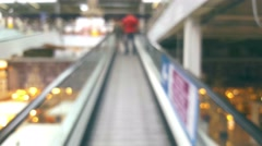 People in shopping mall up the escalator, blurred defocused background Stock Footage
