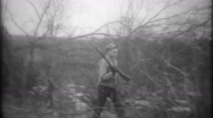 Rabbit hunting with a shotgun in the brush 3527 - vintage film home movie Stock Footage