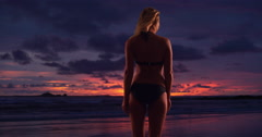 Silhouette of pretty woman standing by the beach at sunset Stock Footage