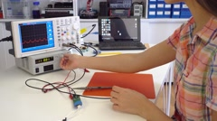 Girl solder and repair electronic device in laboratory Stock Footage