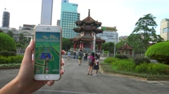 4K Asian woman playing Pokemon Go on App in Asia park, used her smart phone-Dan Stock Footage