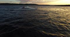 Jet Ski ride off into the sun set on lake Stock Footage