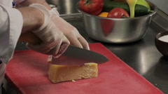 Chef slicing a piece of cheese - stock footage