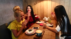 Three beautiful female smile in cafe, talk, tell secrets, eat, d Stock Footage