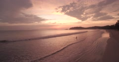 Surfer on The Beach at Sunset on Koh Phayam in Thailand, Push-in Aerial Shot Stock Footage