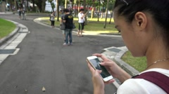 4K Asian people playing Pokemon Go on App in Asia park, used a smart phone-Dan Stock Footage