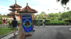 4K Asian woman playing Pokemon Go on App in Asia monument. Used Smart phone-Dan Stock Footage