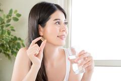 Beautiful asian women healthy diet eating nutritional supplement pill Stock Photos