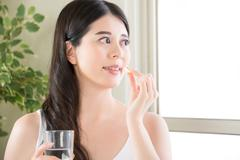 young beautiful asian woman eating nutritional supplement pill for healthy li - stock photo