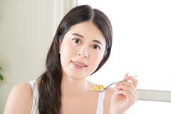 Young beautiful asian woman eating nutritional supplement pill for healthy li Stock Photos