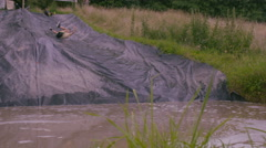 4K Mud race runners on assault course slide down hill into cold muddy water Stock Footage