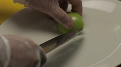 Chef putting curved apple into the plate, close up Stock Footage
