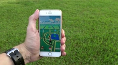 4K Man playing Pokemon Go on App in an Asia park, used smart phone-Dan Stock Footage